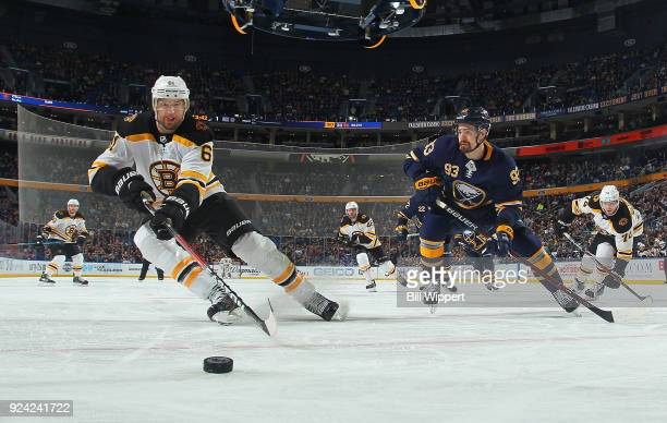 Rick Nash of the Boston Bruins chases the puck along the boards against Victor Antipin of the Buffalo Sabres during the second period of an NHL game...