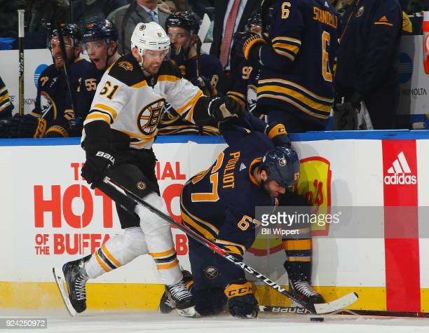 Rick Nash of the Boston Bruins checks Benoit Pouliot of the Buffalo Sabres into the boards during an NHL game on February 25 2018 at KeyBank Center...