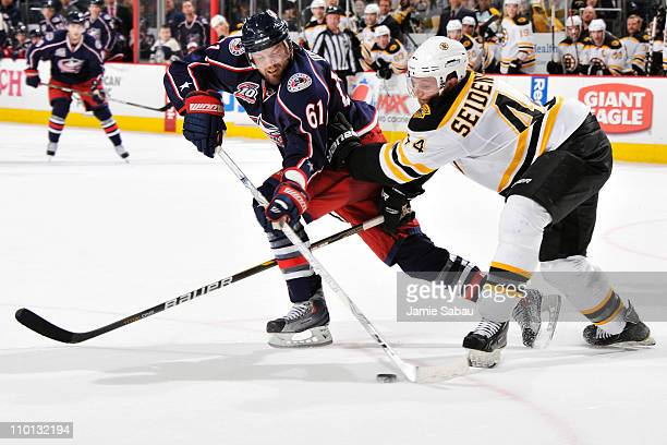 Rick Nash of the Columbus Blue Jackets and Dennis Seidenberg of the Boston Bruins battle for a loose puck during the third period on March 15 2011 at...