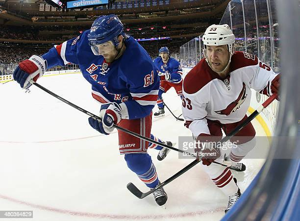 Rick Nash of the New York Rangers and Derek Morris of the Phoenix Coyotes meet along the boards at Madison Square Garden on March 24, 2014 in New...