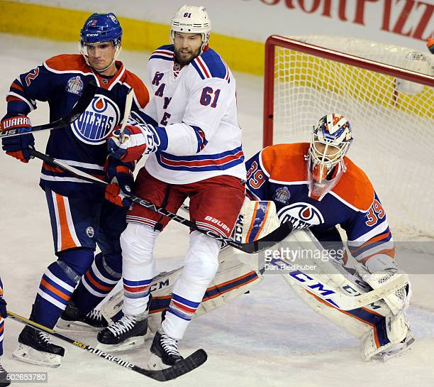 Rick Nash of the New York Rangers battles with Andrej Sekera and goaltender Anders Nilsson of the Edmonton Oilers at Rexall Place on December 11 2015...