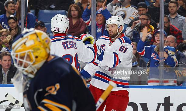 Rick Nash of the New York Rangers celebrates his second period goal with teammate Jimmy Vesey as goaltender Anders Nilsson of the Buffalo Sabres...