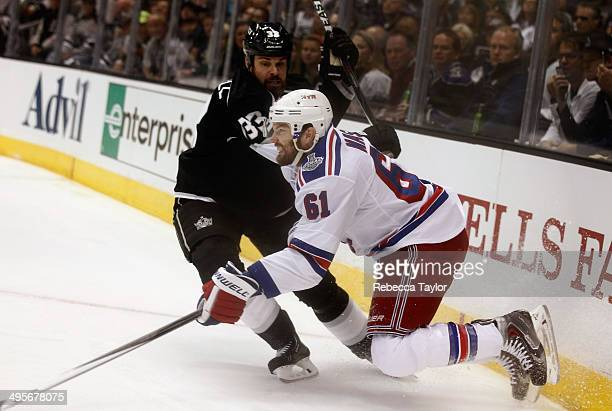 Rick Nash of the New York Rangers gets tripped up by Willie Mitchell of the Los Angeles Kings during the second period of Game One of the 2014...