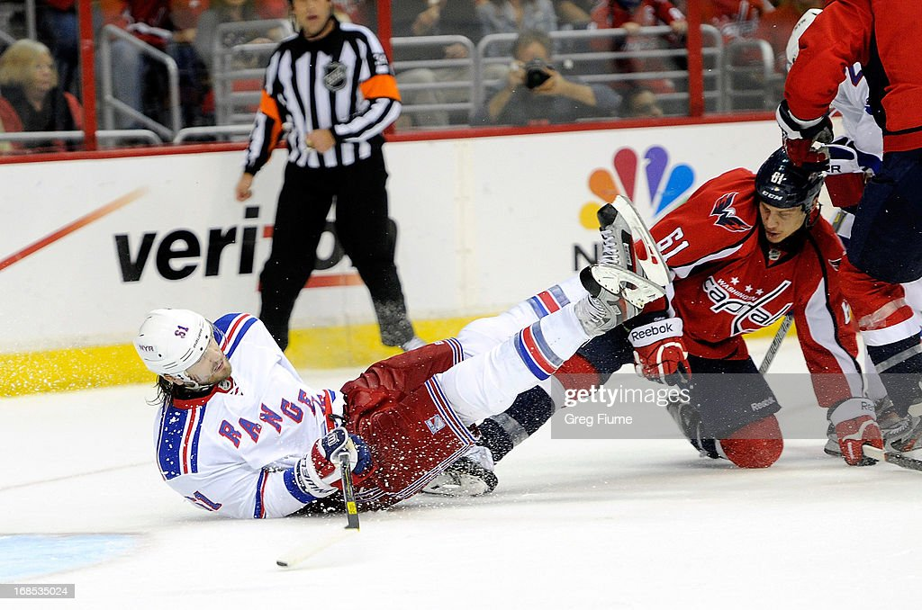 Rick Nash #61 of the New York Rangers is knocked to the ice by Steve Oleksy #61 of the Washington Capitals in overtime of Game Five of the Eastern Conference Quarterfinals during the 2013 NHL Stanley Cup Playoffs at the Verizon Center on May 10, 2013 in Washington, DC.