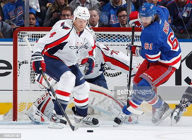 Rick Nash of the New York Rangers looks for the loose puck near John Erskine of the Washington Capitals in Game Three of the Eastern Conference...