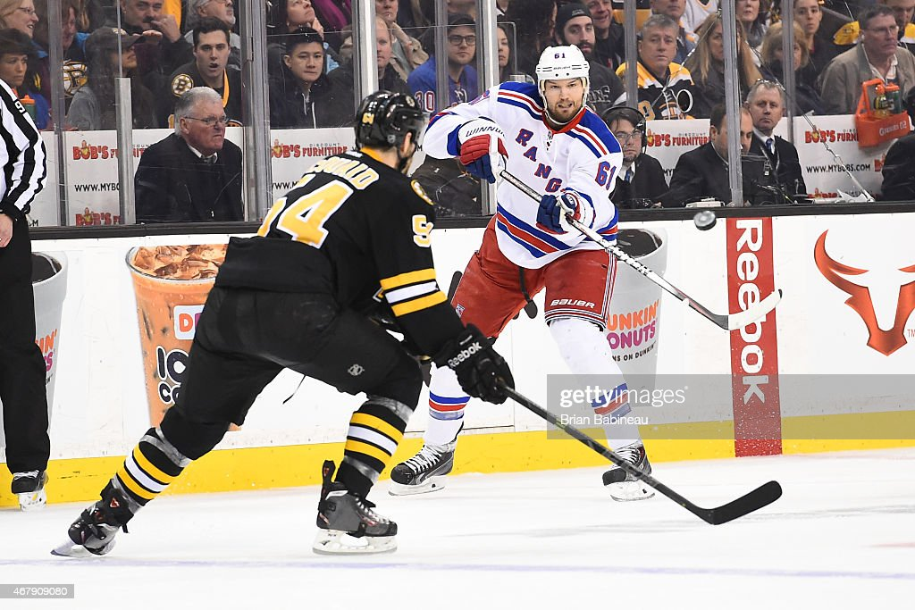 Rick Nash #61 of the New York Rangers passes the puck against Adam McQuaid #54 of the Boston Bruins at the TD Garden on March 28, 2015 in Boston, Massachusetts.
