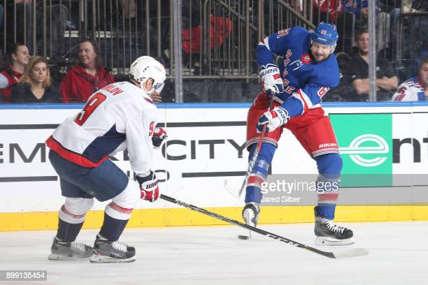 Rick Nash of the New York Rangers shoots the puck against Dmitry Orlov of the Washington Capitals at Madison Square Garden on December 27 2017 in New...