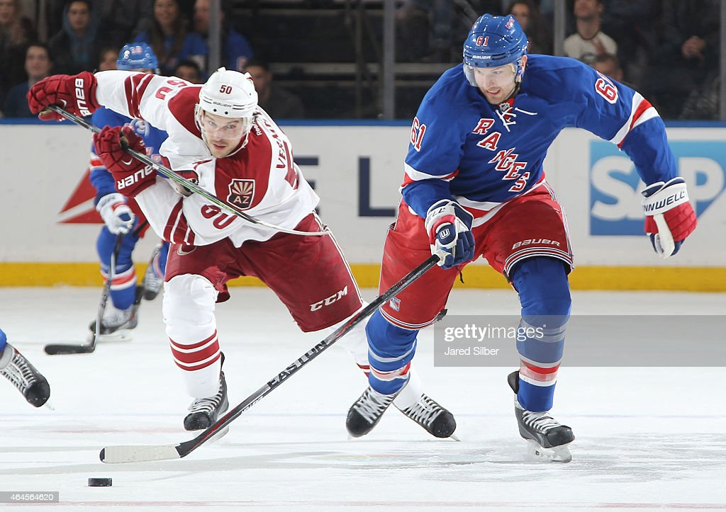 Rick Nash #61 of the New York Rangers skates with the puck against Antoine Vermette #50 of the Arizona Coyotes at Madison Square Garden on February 26, 2015 in New York City.