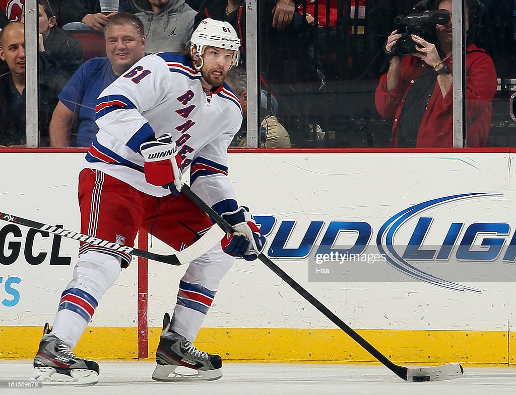 Rick Nash #61 of the New York Rangers takes the puck in the first period against the New Jersey Devils at the Prudential Center on March 19, 2013 in Newark, New Jersey.