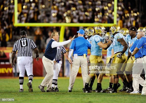 Rick Neuheisel head coach of the UCLA Bruins restrains his players after they nearly had an allout fight with USC Trojans at the end of the NCAA...