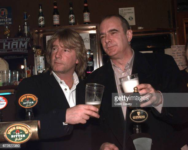 Rick Parfitt and Francis Rossi of rock band Status Quo holding pints of beer behind the bar at the Ruskin Arms in east London 23rd March 1999
