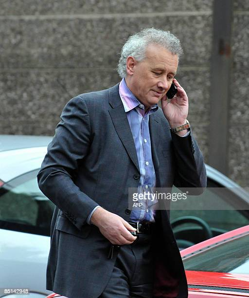 Rick Parry uses his cellphone as he walks out Liverpool's Anfield ground on February 27 2009 He will leave his post as Liverpool FC chief executive...