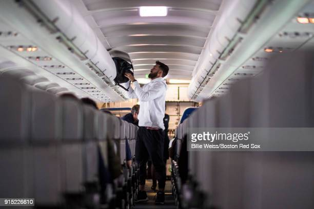 Rick Porcello of the Boston Red Sox stows his bag on the plane en route during a Boston Red Sox hurricane relief trip from Boston Massachusetts to...