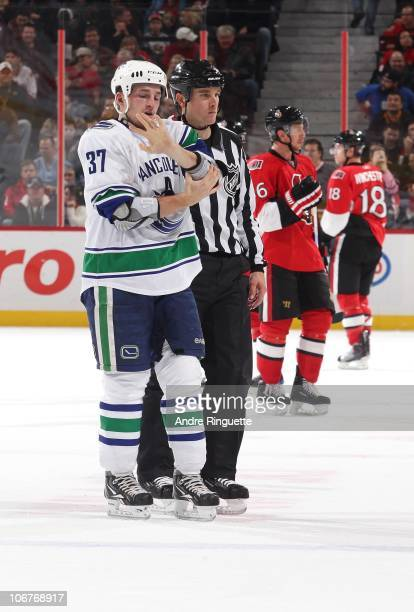 Rick Rypien of the Vancouver Canucks checks out his hands after his second fight of the night during an NHL game against the Ottawa Senators as...