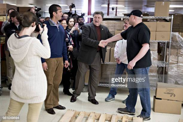 Rick Saccone Republican candidate for the US House of Representatives center shake hands with an employee while touring Sarris Candies with Donald...