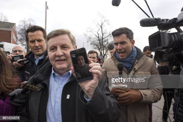 Rick Saccone Republican candidate for the US House of Representatives holds a smartphone while speaking to members of the media after voting at the...