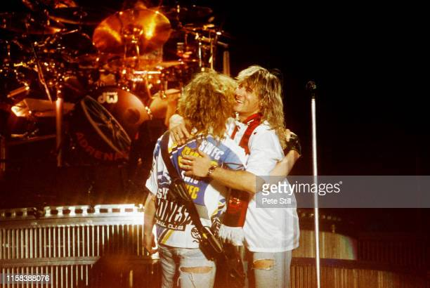 Rick Savage and Joe Elliott of Def Leppard embrace during their performance on stage at The Don Valley Stadium, on June 6th, 1993 in Sheffield,...