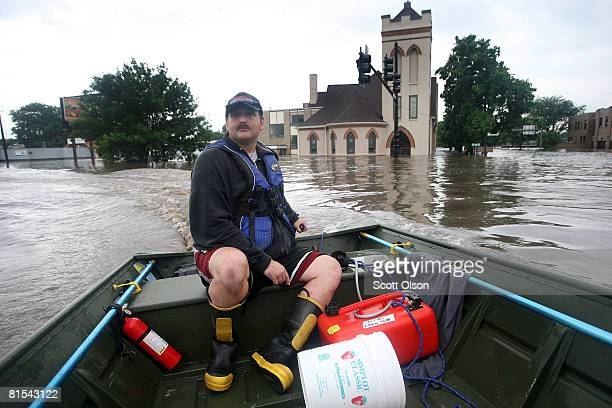 Rick Scott of the Lisbon, Iowa Fire Department surveys the streets searching for flood victims in need of rescue June 12, 2008 in Cedar Rapids, Iowa....