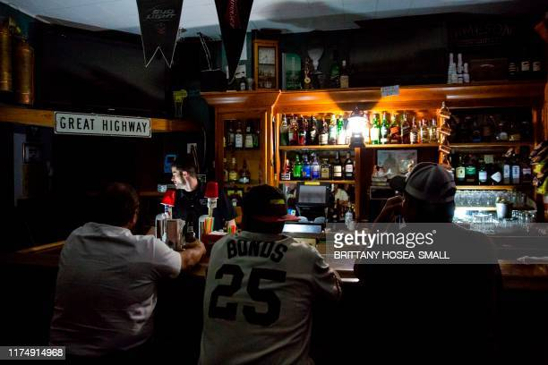 Rick Shaw bartends using light from a lantern at the Town Square Sports Bar in Sonoma California on October 9 during a planned power outage by the...