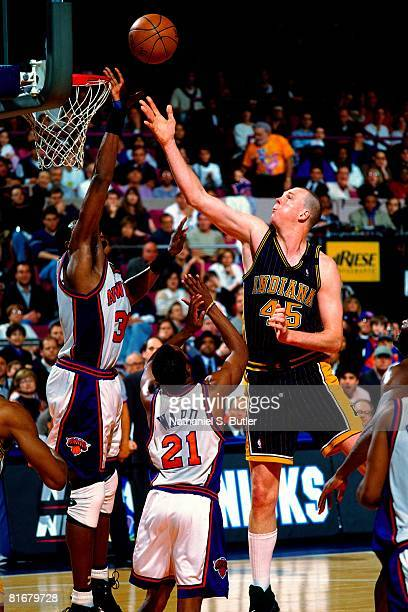 Rick Smits of the Indiana Pacers shoots a layup against Patrick Ewing and Charlie Ward of the New York Knicks in Game Four of the Eastern Conference...