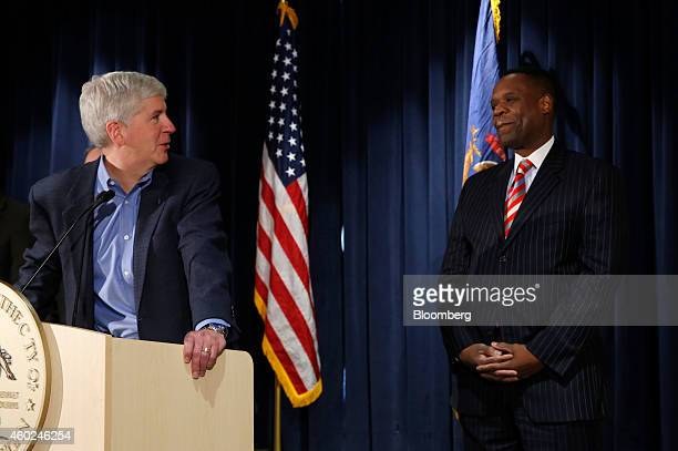 Rick Snyder, governor of Michigan, left, looks toward Kevyn Orr, emergency manager for Detroit, right, during a news conference at police...