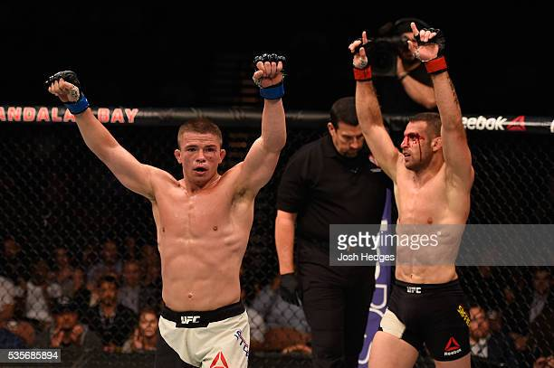 Rick Story and Tarec Saffiedine of Belgium raise their hands after their welterweight bout during the UFC Fight Night event inside the Mandalay Bay...