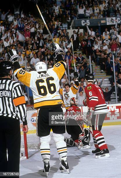 Rick Tocchet and Mario Lemieux of the Pittsburgh Penguins celebrate Tocchet's goal as goalie Ed Belfour and Frantisek Kucera of the Chicago...