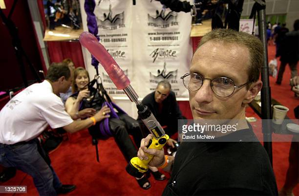 Rick Vanthiel holds a ''Drilldo'' sex toy he designed as a woman sits in the ''Bungee Experience'' harness at the fifth annual Erotica LA adult...