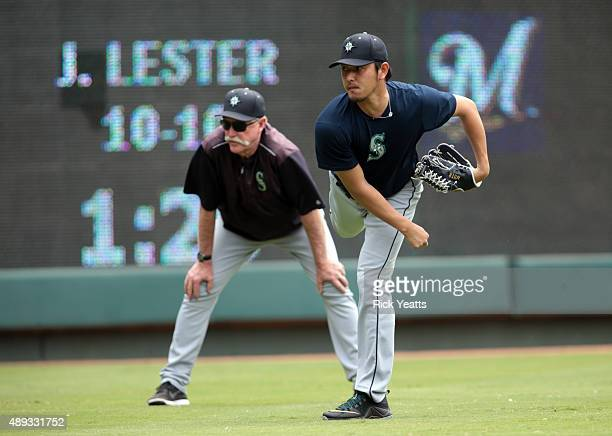 Rick Waits pitching coach of the Seattle Mariners looks on as Hisashi Iwakuma of the Seattle Mariners warms up before the game against the Texas...