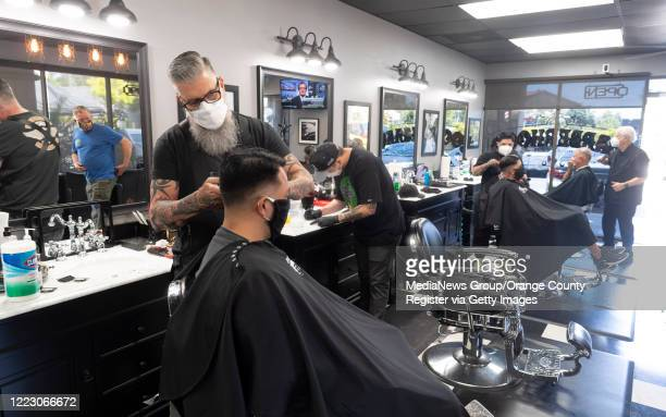 Rick Wood coowner of The BarberHood in Laguna Hills CA cuts hair on Tuesday May 5 2020 The shop is one of the first to reopen and defy the...