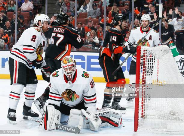 Rickard Rakell and Adam Henrique of the Anaheim Ducks celebrate as Duncan Keith and goalie Anton Forsberg of the Chicago Blackhawks react after...