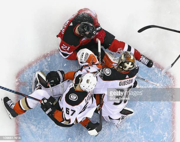 Rickard Rakell and John Gibson of the Anaheim Ducks defend against Kyle Palmieri of the New Jersey Devils at the Prudential Center on January 19 2019...