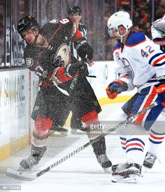 Rickard Rakell of the Anaheim Ducks dumps the puck with pressure from Anton Slepyshev of the Edmonton Oilers in Game Seven of the Western Conference...