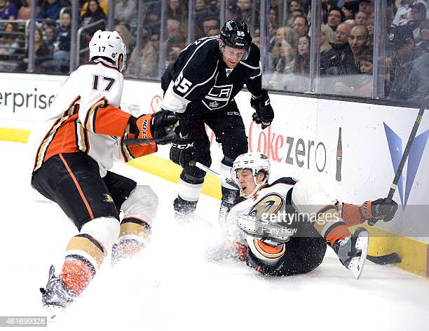 Rickard Rakell of the Anaheim Ducks falls to the ice in front of Jeff Schultz of the Los Angeles Kings and teammate Ryan Kesler during the first...