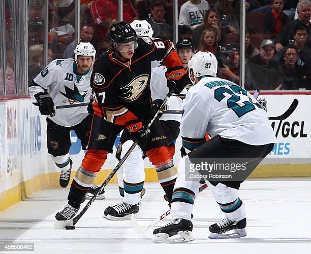 Rickard Rakell of the Anaheim Ducks handles the puck against Scott Hannan of the San Jose Sharks on October 26 2014 at Honda Center in Anaheim...