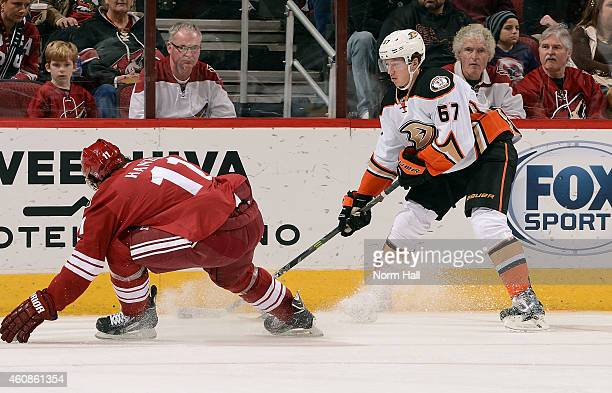 Rickard Rakell of the Anaheim Ducks skates with the puck as Martin Hanzal of the Arizona Coyotes defends during the second period at Gila River Arena...