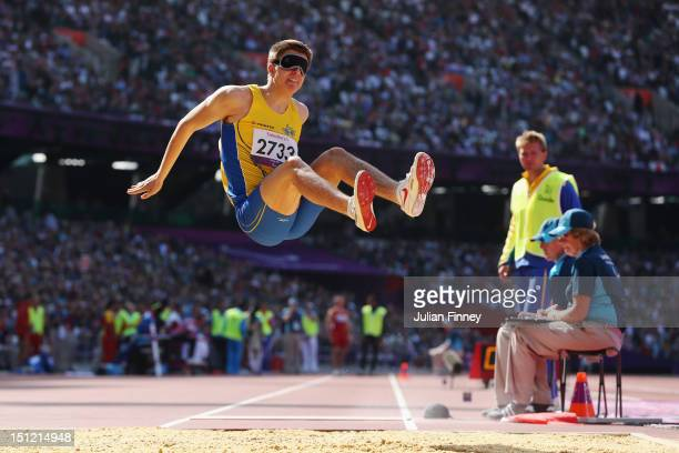 Rickard Straht of Sweden is watched by his guide as he competes in the Men's Long Jump - F11 Final on day 6 of the London 2012 Paralympic Games at...