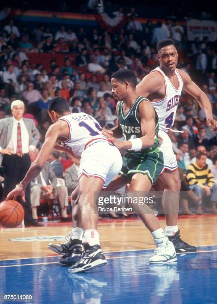 Rickey Green of the Philadelphia 76ers dribbles against Jay Humphries of the Milwaukee Bucks as Rick Mahorn of the 76ers sets a pick during Game 3 of...