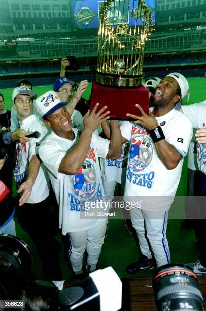 Rickey Henderson and Joe Carter of the Toronto Blue Jays hoist the World Series trophy after defeating the Philadelphia Phillies 86 on Carter's 9th...