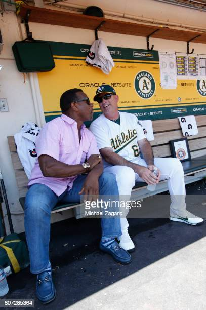 Rickey Henderson jokes around with Coach Steve Scarsone of the Oakland Athletics in the dugout prior to the game against the Houston Astros at the...