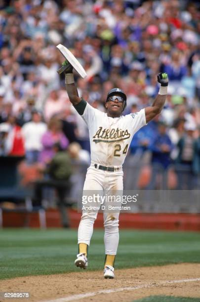 Rickey Henderson of the Oakland Athletics celebrates breaking the 938 stolen base record after stealing third base during a game against the New York...