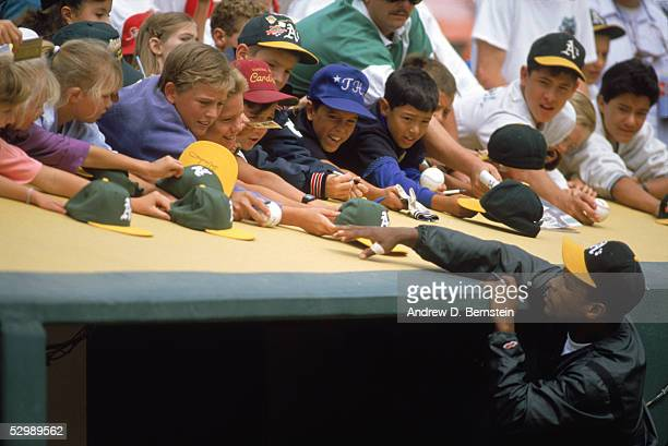 Rickey Henderson of the Oakland Athletics sign autographs for young fans before a game on May,1990 at Oakland Alameda County Coliseum in Oakland,...