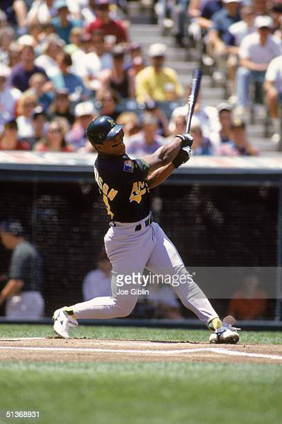 Rickey Henderson of the Oakland Athletics watches the flight of the ball as he follows through his swing during a game against the Cleveland Indians...