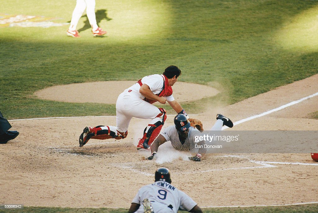 Rickey Henderson #24 of the San Diego Padres dives head first into home plate against Tom Pagnozzi #19 of the St. Louis Cardinals during Game two of the 1996 National League Divisional Series at Busch Stadium on October 3, 1996 in St. Louis, Missouri. The Cards defeated the Padres 5-4.