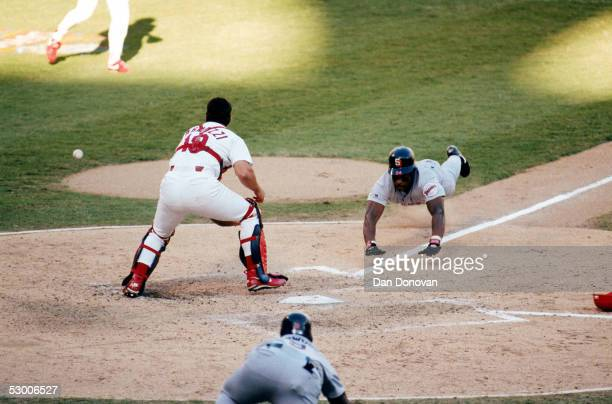 Rickey Henderson of the San Diego Padres dives head first into home plate against Tom Pagnozzi of the St Louis Cardinals during Game two of the 1996...