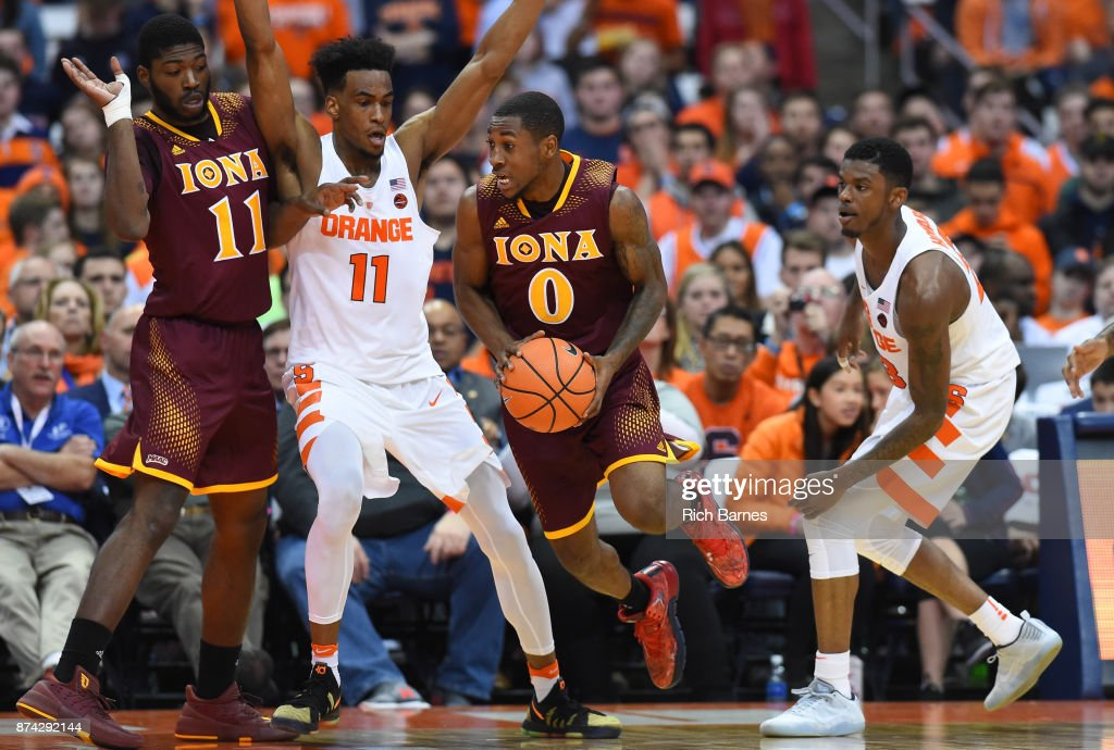 Rickey McGill #0 of the Iona Gaels drives to the basket between Oshae Brissett #11 and Frank Howard #23 of the Syracuse Orange during the first half at the Carrier Dome on November 14, 2017 in Syracuse, New York.