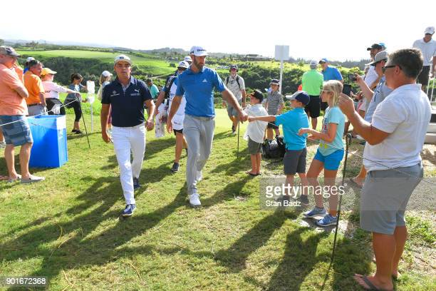 Rickie Fowler and Dustin Johnson greet fans on the ninth hole during the second round of the Sentry Tournament of Champions at Plantation Course at...