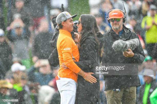 Rickie Fowler and his fiancee Allison Stokke embrace on the eighteenth hole green after the final round of the Waste Management Phoenix Open at TPC...