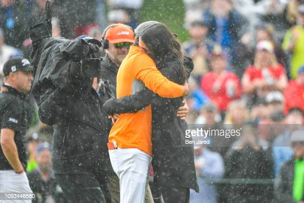Rickie Fowler and his fiancee Allison Stokke hug on the eighteenth hole green after the final round of the Waste Management Phoenix Open at TPC...