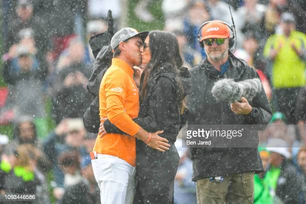 Rickie Fowler and his fiancee Allison Stokke kiss on the eighteenth hole green after the final round of the Waste Management Phoenix Open at TPC...
